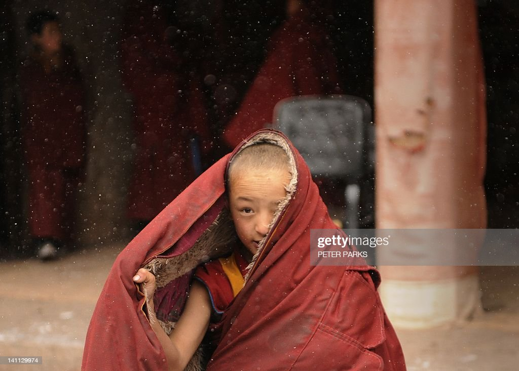 In this picture taken on March 9, 2012, a young Tibetan monk covers up against the snow after taking part in a ceremony at Lajia Monestry in China's northwest Qinghai province. Overseas rights groups say three Tibetans have self-immolated in China in recent days as Beijing tightens security ahead of the sensitive anniversary of deadly 2008 riots. AFP PHOTO/Peter PARKS