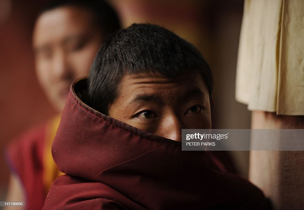 In this picture taken on March 9, 2012, A young Tibetan monk looks on after taking part in a ceremony at Lajia Monestry in China's northwest Qinghai province. Overseas rights groups say three Tibetans have self-immolated in China in recent days as Beijing tightens security ahead of the sensitive anniversary of deadly 2008 riots. AFP PHOTO/Peter PARKS