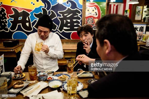 In this picture taken on March 9 men smoke cigarettes during lunch in a restaurant in the Yurakuchu neighbourhood of Tokyo Japan is moving to pass...