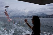 In this picture taken on May 10 a woman throws offerings into the sea while onboard a ferry sailing to Joss House temple to celebrate the Tin Hau...