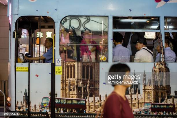In this picture taken on May 24 a tram is seen decorated with Britain's Houses of Parliament as commuters travel during the evening in Hong Kong From...