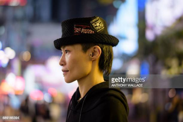 In this picture taken on May 24 Jill a hairstylist poses while wearing a small British national flag design on a badge which she sewed onto her hat...