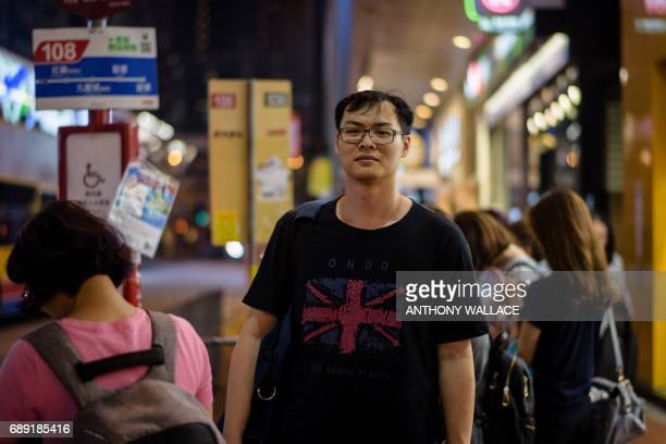 In this picture taken on May 24 Ken a 27yearold builder poses while wearing a Tshirt with a British national flag design as he waits for his bus...