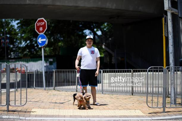 In this picture taken on May 24 Lok who works with a small business poses with his dogs while wearing a Tshirt with a British flag design in Hong...
