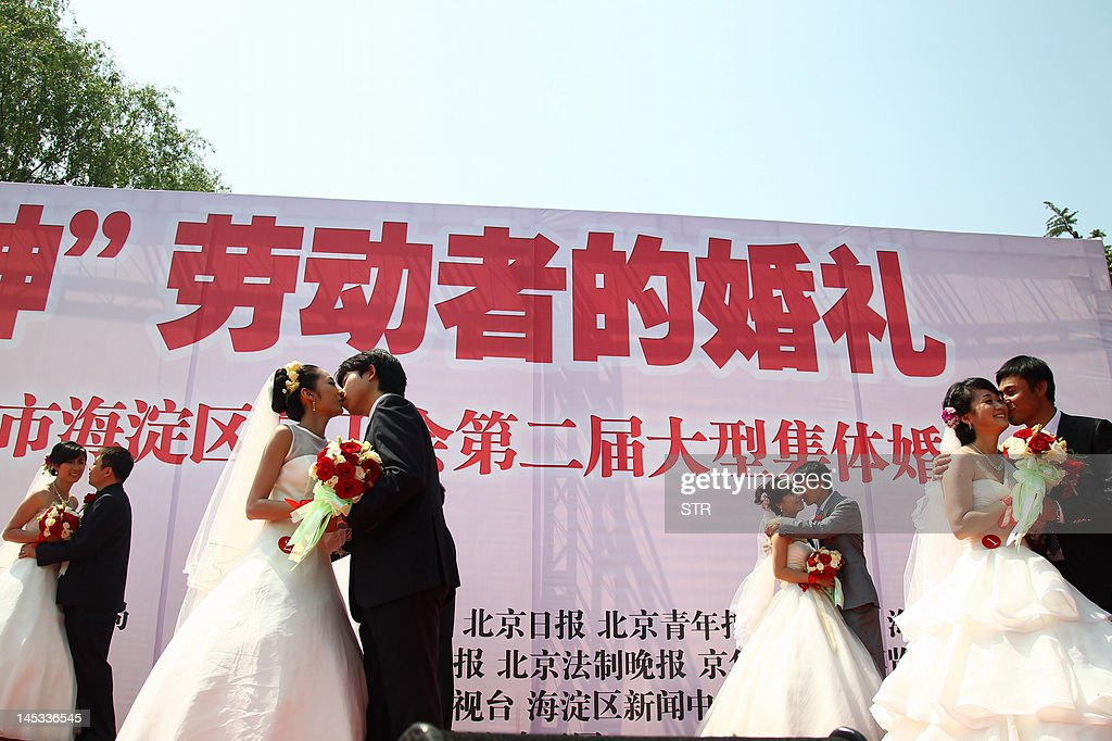 In this picture taken on May 26, 2012 shows a group of 18 Chinese couples kiss as they take part in a mass wedding ceremony in Beijing. China's wedding market, estimated to be worth nearly 60 billion USD, where 10 million weddings take place annually -- five times as many as in the US, is by far the world's largest. CHINA