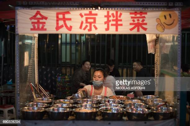 In this picture taken on May 27 a street food vendor waits for customers in Beijing Activity in China's key factory sector expanded in May official...