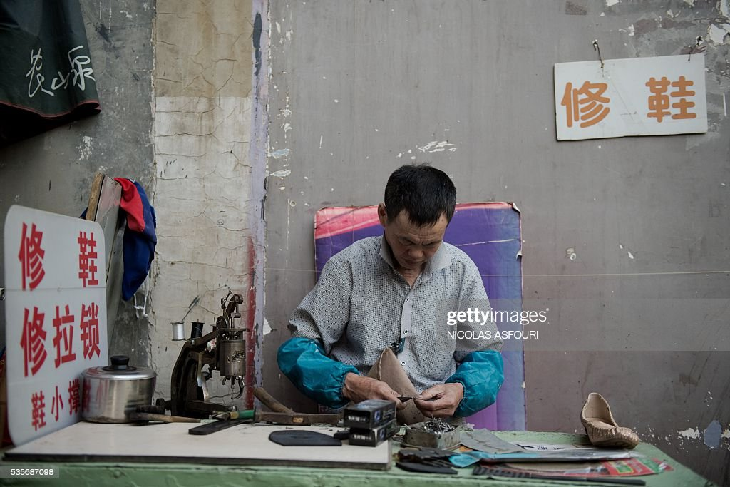 In this picture taken on May 29, 2016, a cobbler repairs a pair of shoes on a street in Beijing. / AFP / NICOLAS
