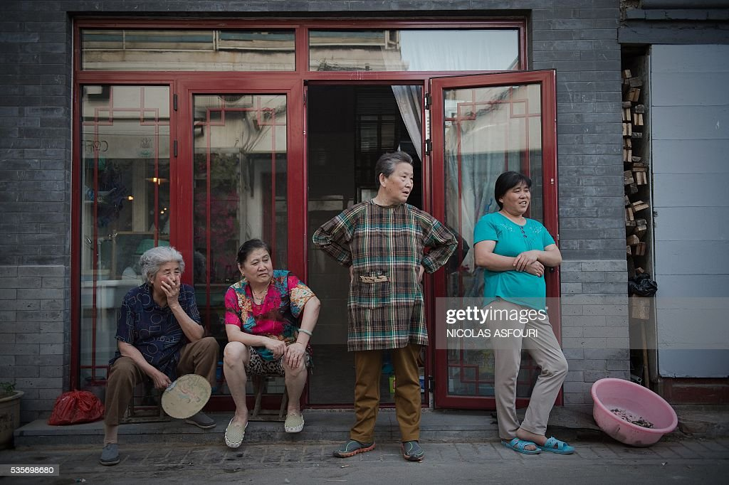 In this picture taken on May 29, 2016, a group of woman stand on a street as they look at a neighbor (not seen) trying to lift a heavy object out of his house in Beijing. / AFP / NICOLAS