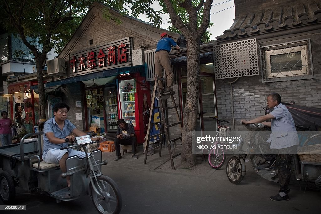 In this picture taken on May 29, 2016, a man eats a sandwich (C,L) as another repairs a roof (C,R) in Beijing. / AFP / NICOLAS
