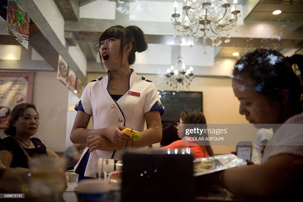 In this picture taken on May 29, 2016, a waitress (C) yawn as she waits to take an order from a customer (R) inside a restaurant in Beijing. / AFP / NICOLAS