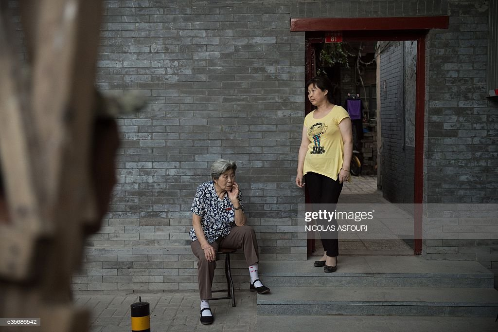 In this picture taken on May 29, 2016, an elderly woman (C) sits outside her house next to a woman (R) in Beijing. / AFP / NICOLAS