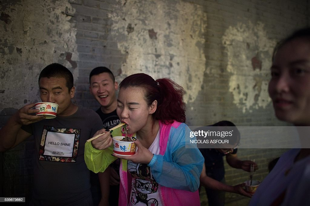 In this picture taken on May 29, 2016, people eat noodles on a street in Beijing. / AFP / NICOLAS