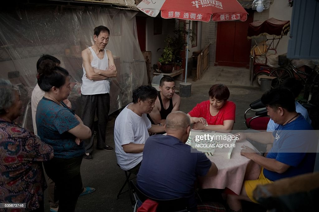 In this picture taken on May 29, 2016, people play Mahjong outside their house on a street in Beijing. / AFP / NICOLAS
