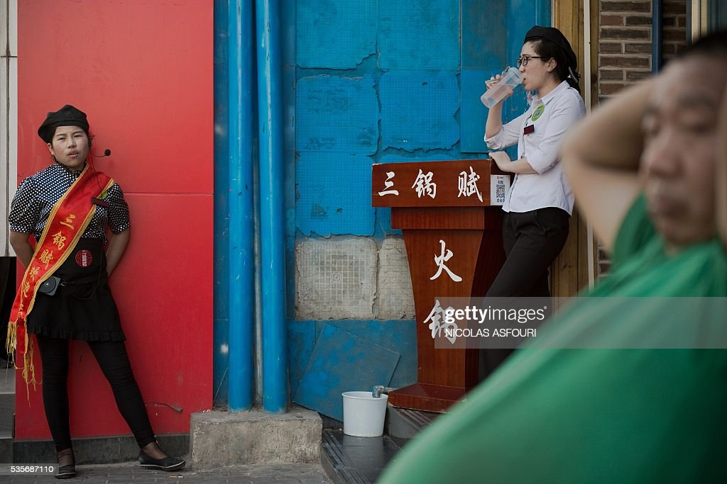 In this picture taken on May 29, 2016, two restaurant workers wait to welcome customers (Rand L, back) outside a restaurant as a man (R, front) sits and rest in a street in Beijing. / AFP / NICOLAS