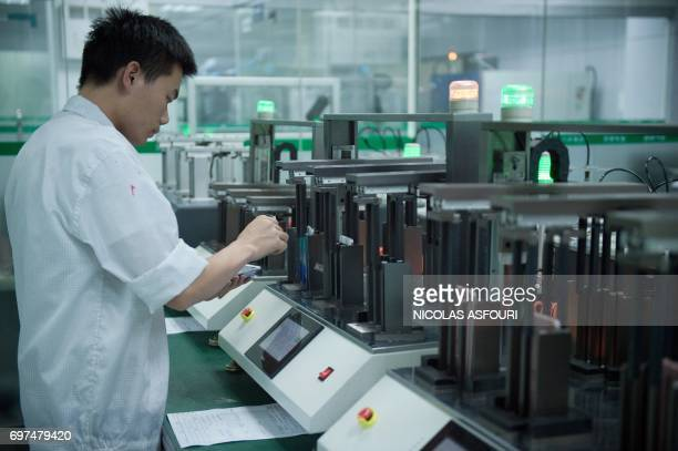In this picture taken on May 8 a worker operates a machine at the testing facility of the Oppo factory in Dongguan Oppo which started out making DVD...