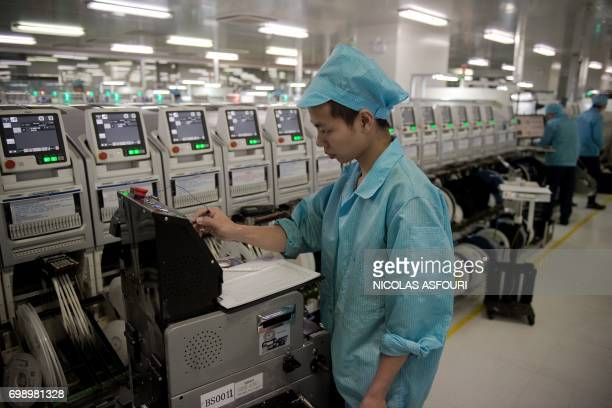 In this picture taken on May 8 a worker operates a machine at the Oppo factory in Dongguan Chinese smartphone maker Oppo began life selling DVD...