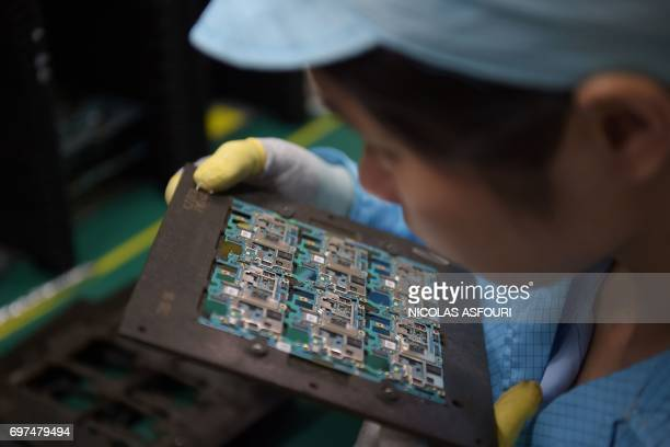 In this picture taken on May 8 smartphone chip component circuits are handled by a worker at the Oppo factory in Dongguan Oppo which started out...