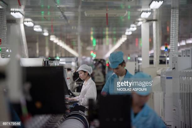 In this picture taken on May 8 workers build smartphone chip component circuits at the Oppo factory in Dongguan Oppo which started out making DVD...