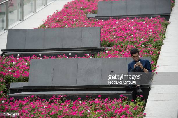 In this picture taken on May 9 a man sits on a bench while using his smartphone outside a shopping mall complex in Shenzhen Oppo which started out...
