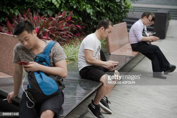 In this picture taken on May 9 people use their smartphones along a street in the southern Chinese city of Shenzhen Chinese smartphone maker Oppo...