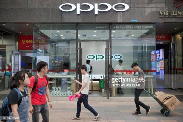 In this picture taken on May 9 people walk in front of an Oppo shop in Shenzhen Oppo which started out making DVD players in the southern...