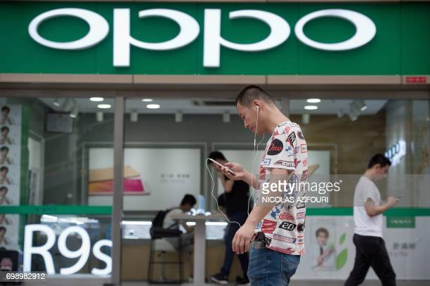 In this picture taken on May 9 people walk in front of an Oppo shop in Shenzhen Chinese smartphone maker Oppo began life selling DVD players in the...