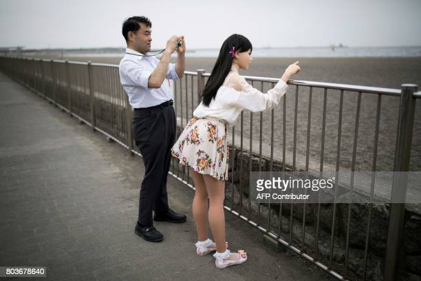 In this picture taken on May 9 physiotherapist Masayuki Ozaki takes pictures of his silicone sex doll Mayu in Tokyo Bay Around 2000 of the lifelike...