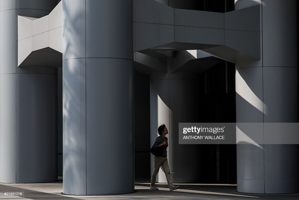In this picture taken on November 1, 2016, a pedestrian walks past an entrance of the HSBC headquarters building in Hong Kong. HSBC said on November 7 its third quarter adjusted pretax profit rose seven percent from a year ago to USD 5.59 billion, beating expectations. / AFP / ANTHONY