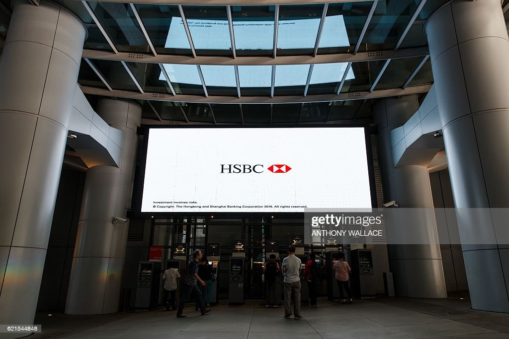 In this picture taken on November 1, 2016, customers use automatic teller machines at the HSBC headquarters building in Hong Kong. HSBC said on November 7 its third quarter adjusted pretax profit rose seven percent from a year ago to USD 5.59 billion, beating expectations. / AFP / ANTHONY
