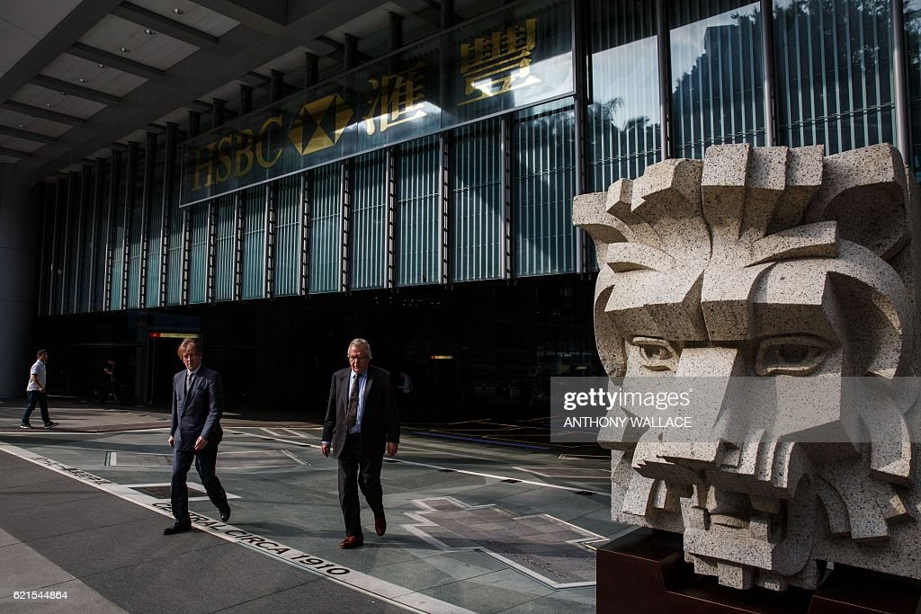 In this picture taken on November 1, 2016, people walk outside the HSBC headquarters building in Hong Kong. HSBC said on November 7 its third quarter adjusted pretax profit rose seven percent from a year ago to USD 5.59 billion, beating expectations. / AFP / ANTHONY