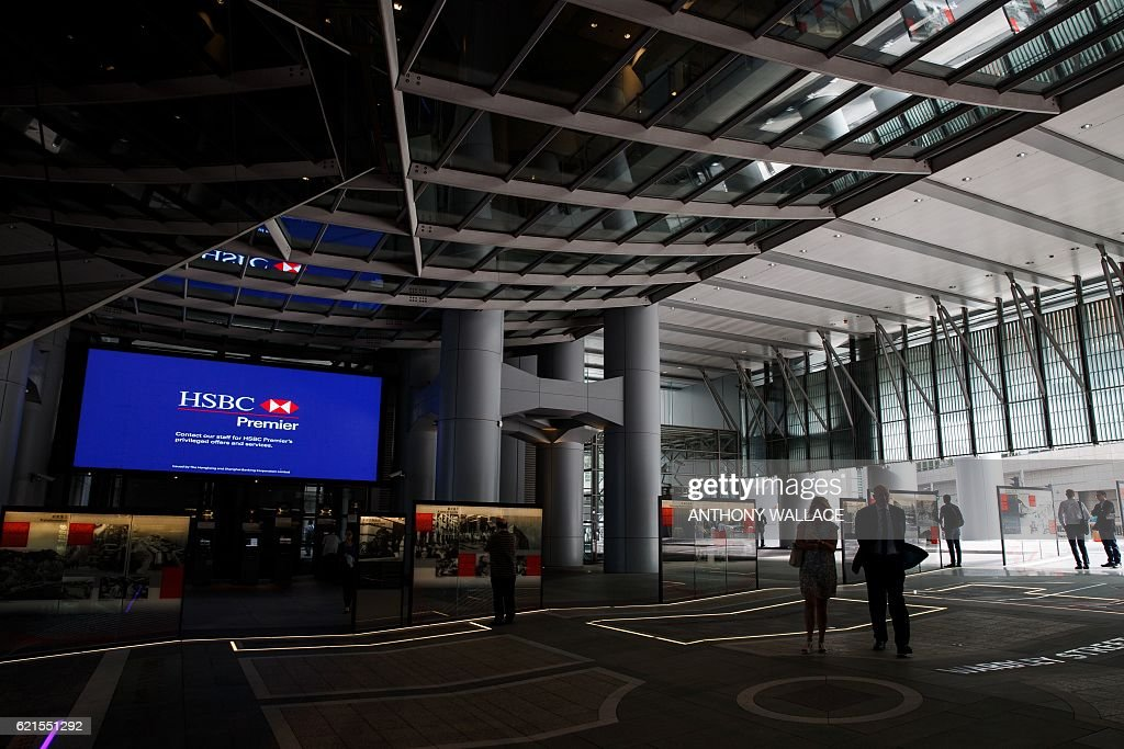 In this picture taken on November 1, 2016, people walk through the the HSBC headquarters building in Hong Kong. HSBC said on November 7 its third quarter adjusted pretax profit rose seven percent from a year ago to USD 5.59 billion, beating expectations. / AFP / ANTHONY