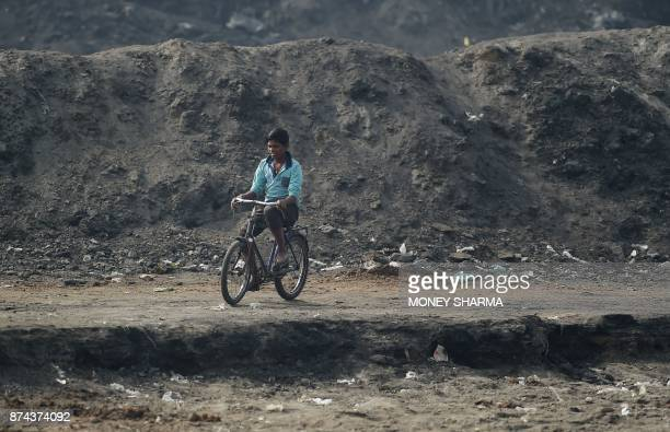 In this picture taken on November 13 an Indian youth cycles past waste from brass factories dumped on the banks of Ramganga river in Moradabad In the...