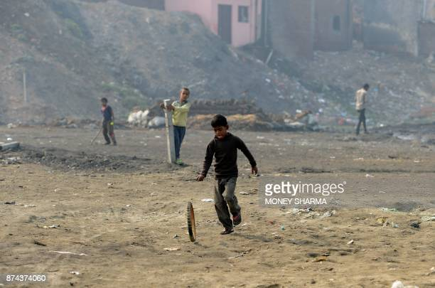 In this picture taken on November 13 Indian children play near waste from brass factories that is dumped on the banks of Ramganga river in Moradabad...