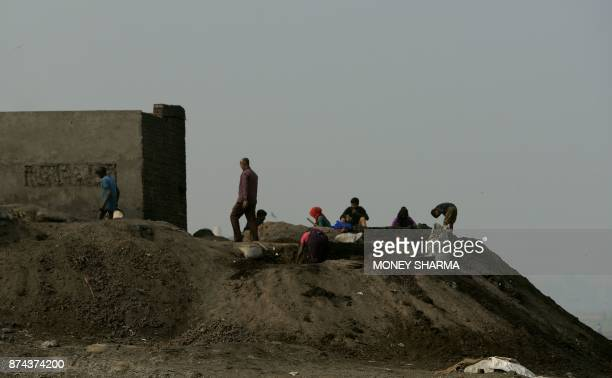 In this picture taken on November 13 Indian workers work at a dumping site outside a brass factory on the banks of Ramganga river in Moradabad In the...