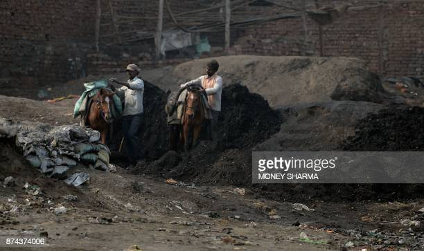 TOPSHOT In this picture taken on November 13 people work on the banks of Ramganga river as they collect scrap metal left as waste by brass factories...