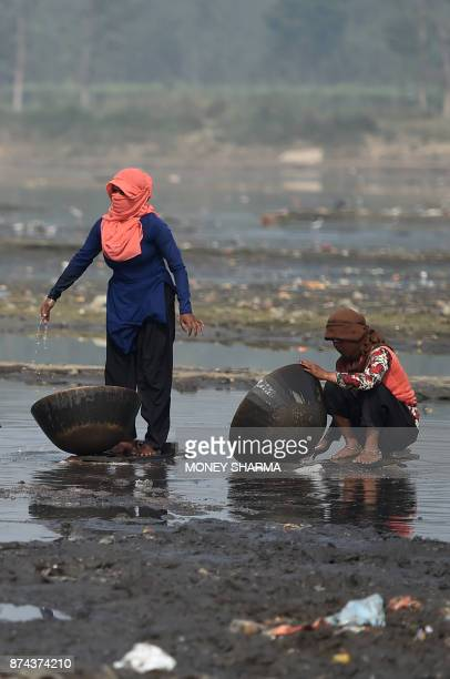In this picture taken on November 13 people work on the banks of Ramganga river as they collect scrap metal left as waste by brass factories in...