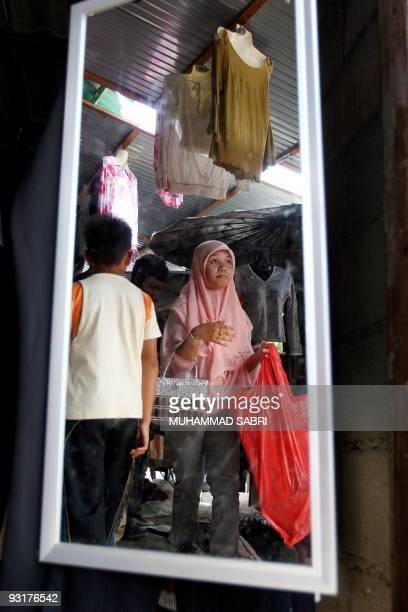 In this picture taken on November 14 a Thai Muslim woman shops at a secondhand market in Thailand's southern province of Yala Thai consumer...