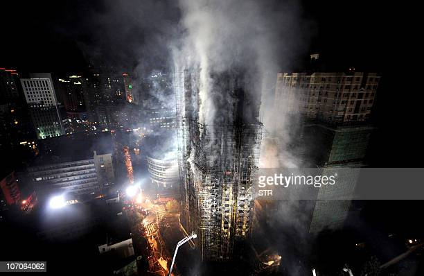 In this picture taken on November 15 Chinese firefighters extinguish a huge fire which engulfed a highrise building in Shanghai after construction...