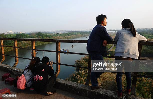 In this picture taken on November 20 2014 people relax on the centuryold Long Bien bridge crossing over the Red River in Hanoi Built in early 19th...