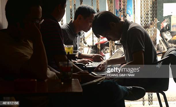 In this picture taken on November 26 men use tablets and laptops to check news over wifi at a coffee shop in Hanoi Vietnam's Prime Minister Nguyen...