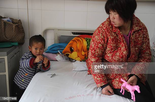 In this picture taken on November 28 a Chinese woman accompanies her child who was infected with hepatitis C at a hospital in Hefei east China's...