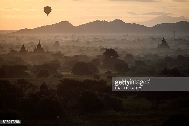 TOPSHOT In this picture taken on November 28 a hotair balloon carrying tourists sails over the archeological site at sunrise in Bagan Located in...