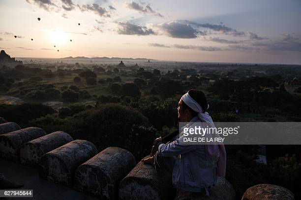 In this picture taken on November 28 a man watches as hotair balloons carrying tourists sail over the archeological site at sunrise in Bagan Located...