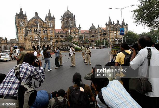 In this picture taken on November 28 Indian media representatives look on as police officials stand alert outside the Chatrapathi Shivaji Terminus in...