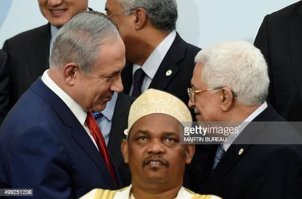 In this picture taken on November 30 2015 Israeli Prime Minister Benjamin Netanyahu talks with Palestine's president Mahmud Abbas behind Comoros'...