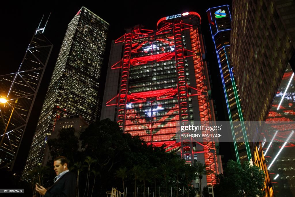 In this picture taken on November 4, 2016, a pedestrian walks in front of the HSBC headquarters building (in red) in Hong Kong. HSBC said on November 7 its third quarter adjusted pretax profit rose seven percent from a year ago to USD 5.59 billion, beating expectations. / AFP / ANTHONY