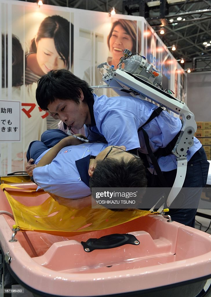 In this picture taken on November 6, 2013, a Japanese elderly care company Asahi Sun Clean employee (top) wearing a power suit, called 'Muscle Suit' powered by compressed air stored in an air tank on his back, lifts a fellow worker during a demonstration at the annual Internatinal Robot Exhibition in Tokyo. Pneumatic muscle suits and a walking stick that behaves like a guide dog competed for attention with an industrial robot that can paint fingernails at a huge expo in Tokyo on November 7, 2013. AFP PHOTO / Yoshikazu TSUNO