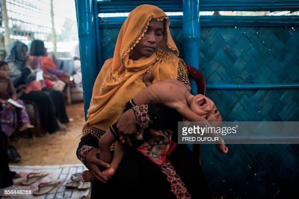 TOPSHOT In this picture taken on October 1 a Rohingya Muslim refugee holds her child as she waits to see a doctor at a medical centre at Balukhali...