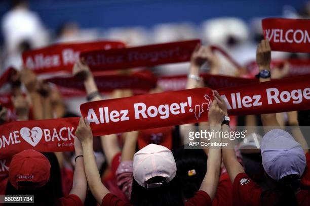 TOPSHOT In this picture taken on October 11 supporters of Roger Federer of Switzerland shout his name during his men's second round singles match...