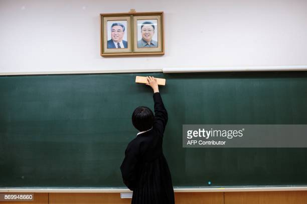 TOPSHOT In this picture taken on October 13 a student cleans the blackboard under portraits of late North Korean leaders Kim Il Sung and Kim Jong Il...